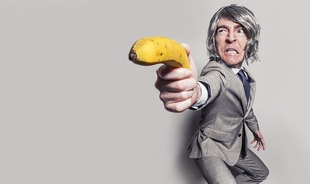 suited business man pointing a banana